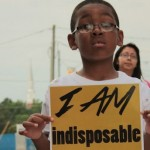 "Young African-American boy holds sign that reads ""I AM indisposable."""