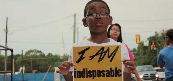 """Young African-American boy holds sign that reads """"I AM indisposable."""""""