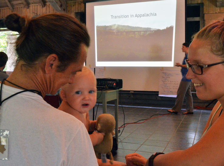 Clear Creek community members Mitch Barrett, Melody Youngblood, and their son River get ready for a presentation on Transition in Appalachia. Photo: Nicole Garneau, 2015.