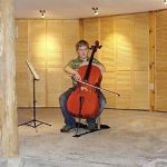 A young cellist demonstrates his skills at the Fall Back in Time yearly Azule potluck-open house.